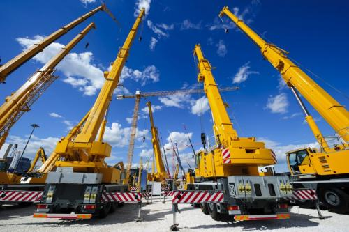 Mobile construction cranes with yellow telescopic arms and big tower cranes in sunny day with white clouds and deep blue sky on background, heavy industry